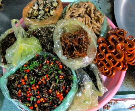 Cambodian market treats: crikets, frogs, snakes, chicken feet and eggs.